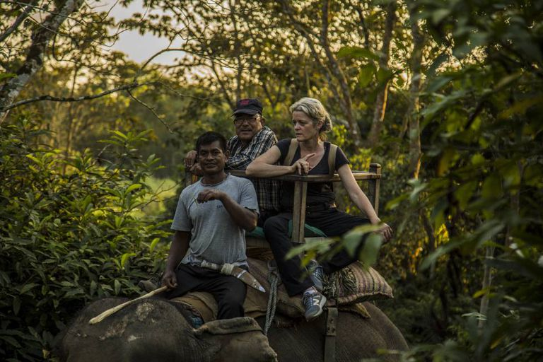 Veterinarian Deborah McCauley and Bishnu Lama on an elephant in Chitwan.