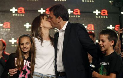 Sergio Massa, mayor of Tigre near Buenos Aires, kisses his wife Malena next to their children after the results of Sunday's legislative elections were announced.