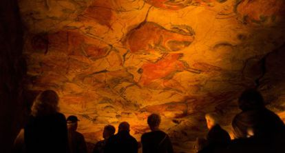 A group of visitors observes the replica of the world-famous cave paintings in Santillana del Mar.
