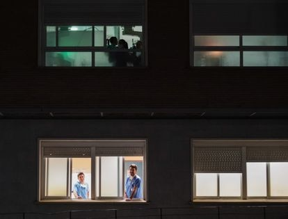 Health workers in Seville come to the window of the Virgen del Rocío hospital to hear the applause of the public on Saturday night.