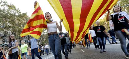 Various people carry a flag through the streets of Barcelona during the strikes.
