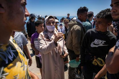 A woman shows a photo of her child to migrants on a beach in Fnideq.