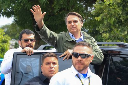 Jair Bolsonaro greets supporters after casting his vote.