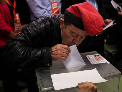A man kisses his ballot paper before voting in Barcelona.