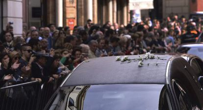 Hundreds of people line the streets of Seville as the funeral car of the Duchess of Alba passes.