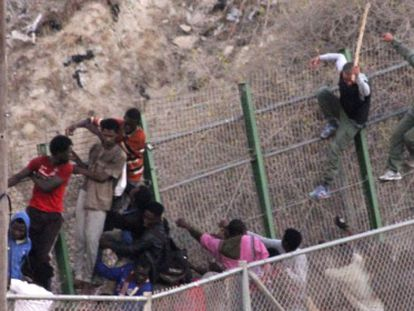 Moroccan police beat immigrants at the border fence on July 18.