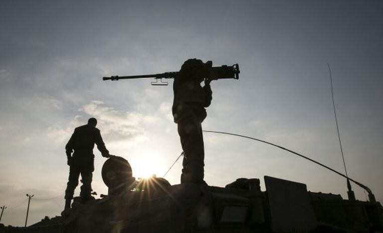 An Israeli soldier holds a weapon near the Gaza Strip.