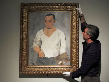 A gallery employee adjusts Picasso's 'Self-portrait with palette' at the Fundación Mapfre exhibition in Madrid.