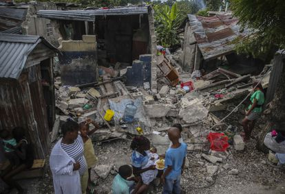 A family outside homes that were destroyed by an earthquake on Saturday.