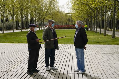 Men wearing face masks chat in the Lineal del Manzanares park in Madrid, in a file photo from March.