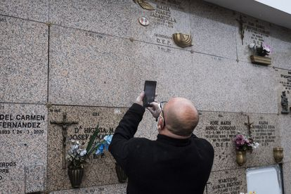 One of sons of former boxer Manuel Álvarez takes a photograph of the marker on the niche.