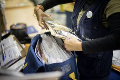 A mail service employee prepares a cart for a delivery round.