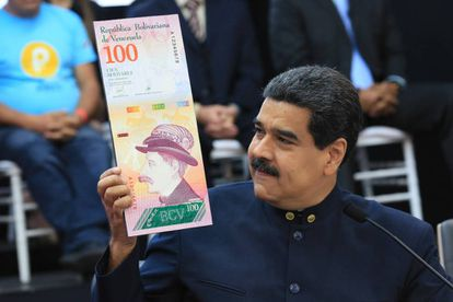 Venezuela's President Maduro with an image of the new Venezuelan banknote, after getting rid of three zeros from the currency.
