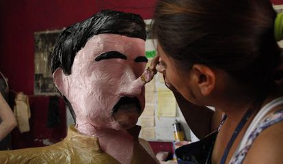 An artist puts the finishing touches on an 'El Chapo' piñata in Tamaulipas.