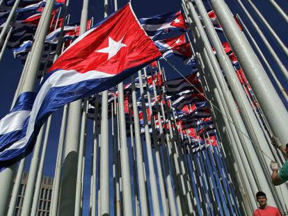 Workers hoist Cuban flags outside the US Interests Section in Havana on December 30.