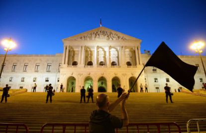A protestor waves a black flag during a demonstration in front of the parliament building in Lisbon on Saturday.