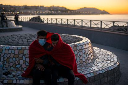 Two young migrants shield from the cold near El Tarajal beach.