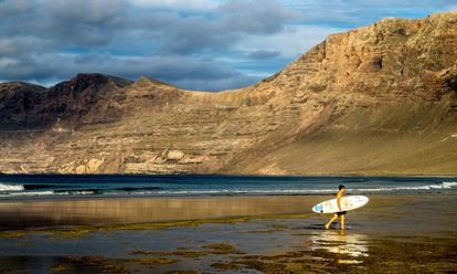 A surfer on Famara cove, on the Spanish island of Lanzarote.