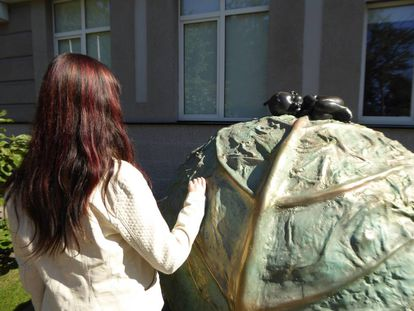 A surrogate mother in Kiev with a sculpture representing the legend that babies come from cabbages.