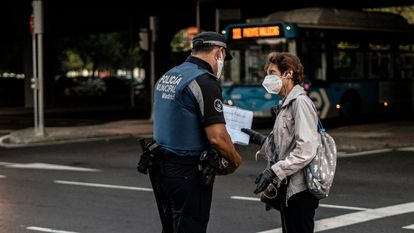 Police security checks in Puente de Vallecas, where residents have been confined in a bid to curb contagion.