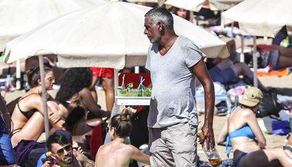 A man sells mojitos on Barcelona's Barceloneta beach.