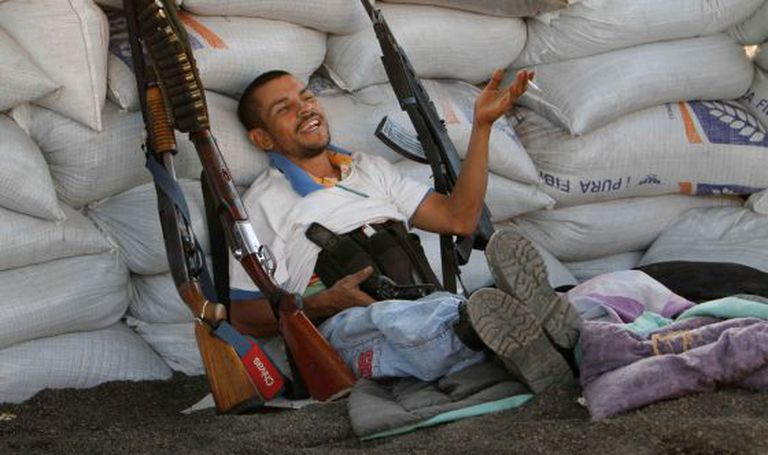A member of the self-defense force relaxes at his post in Apatzingán.