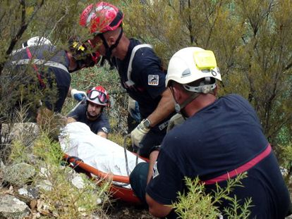 Firefighters salvage the body of Víctor Cabedo from the mountainside last week.