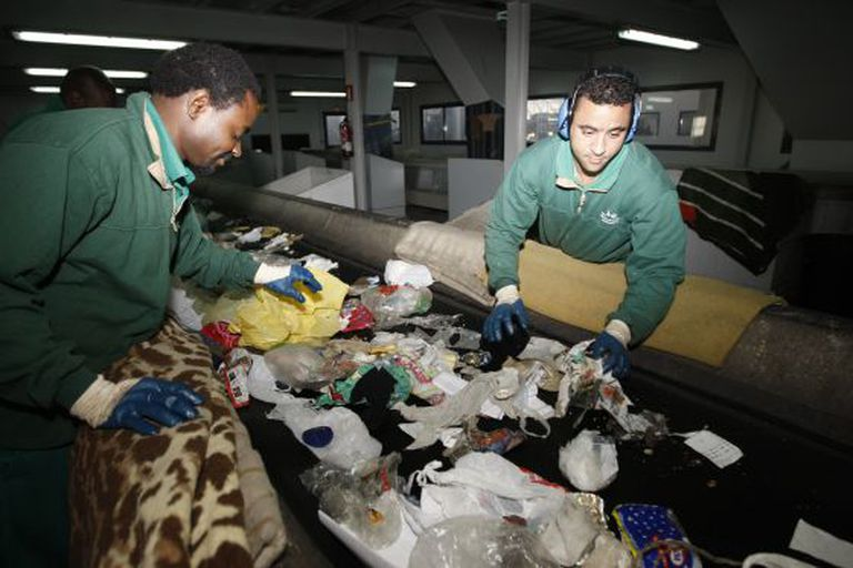 Two workers manually separate garbage at the Valdemíngomez waste plant.