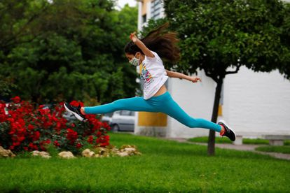 A young girl jumps in a street of Córdoba.