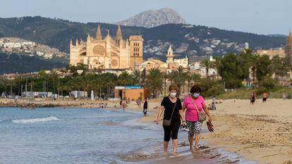 Two women wear masks walk as they take a walk on a beach in Mallorca.
