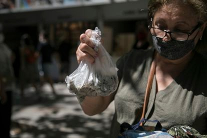 A woman shows off the pesetas she was going to exchange at the Bank of Spain on Tuesday.