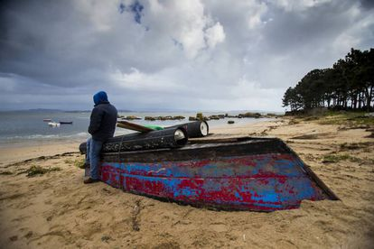 A poacher on the Arousa estuary leans on a boat used for the nightly raids.