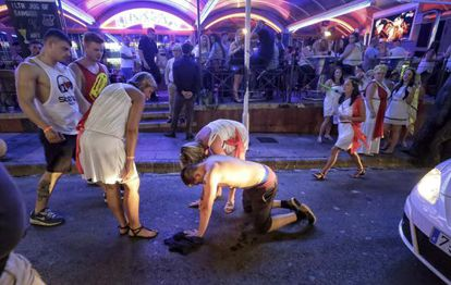A drunk tourist falls to the floor in Punta Ballena, Magaluf in the early hours of a Saturday morning.
