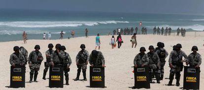 Police form a blockade on Monday during the bid-awarding ceremony at a nearby hotel on Barra de Tijuca beach in Rio de Janeiro.