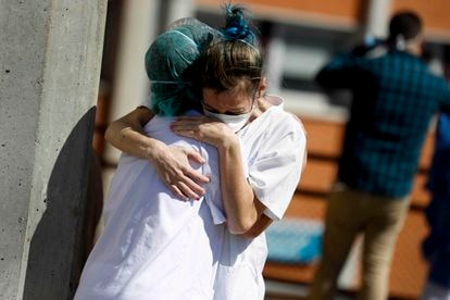 Two health workers hug outside the Severo Ochoa hospital in Madrid in March.