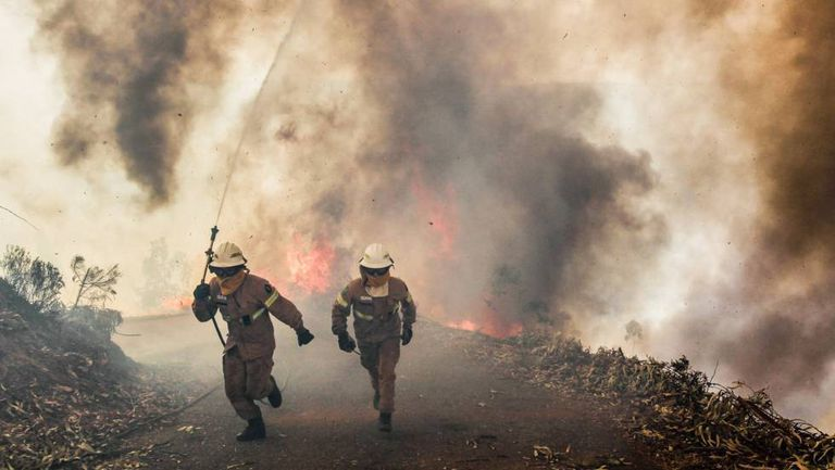 Firefighters flee the flames in Portugal.