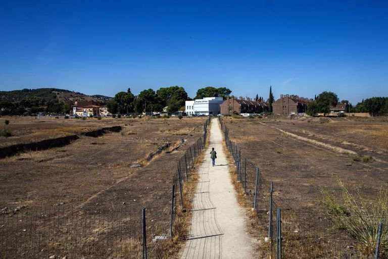 A woman walks on the path that cuts through the Vega Baja archaeological site.