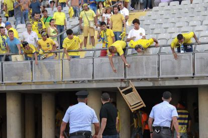 Las Palmas fans throw chairs from the stands.