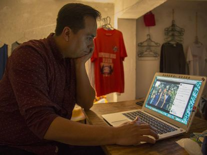 Jesús Ortiz looks at a photo of his family after being deported to Mexico.