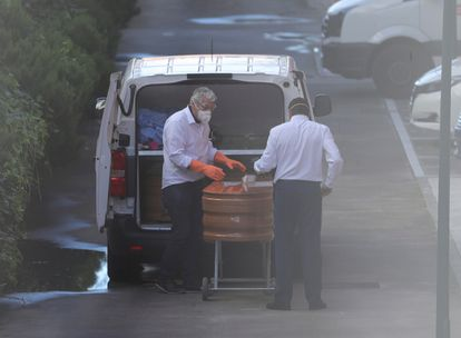 Workers remove a coffin from a senior care home in Valdemoro.