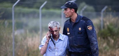 A police officer escorts Francisco Garzón, the train driver on the crashed Alvia, moments after the accident.