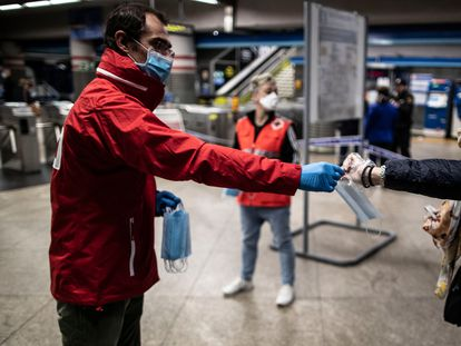 A Red Cross member hands out face masks in Atocha train station in Madrid.