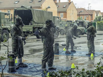 Soldiers disinfect their uniforms after entering a senior residence in Madrid.
