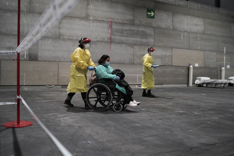 A patient is taken to the Ifema convention center, which has been converted into a temporary field hospital.