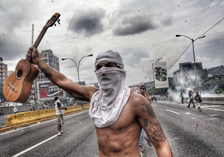 Artist Tomás Vivas, 29, holds up a traditional Venezuelan 'cuatro' instrument during a protest in Caracas.
