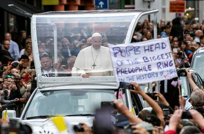 An activist holds up a sign during the pope's visit to Dublin earlier this year.