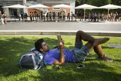 A tourist takes a break while people stand in line outside the Prado museum.