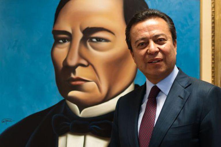 César Camacho Quiroz, stands before a portrait of Benito Juárez.