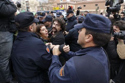Policemen pull protestor Julia Alsinet out of the crowd at an escrache protest outside a PP deputy's home in Madrid last week.