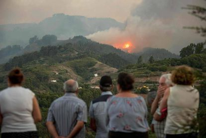 Residents observe smoke billowing from a forest fire raging near Montana Alta on the island of Gran Canaria.